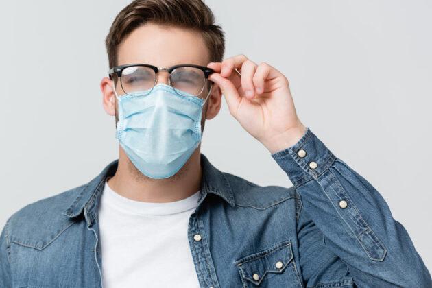 Mann mit Maske und beschlager Brille